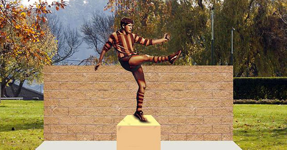 bronze statue of a man kicking a football