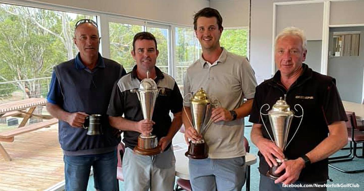 four men holding trophies