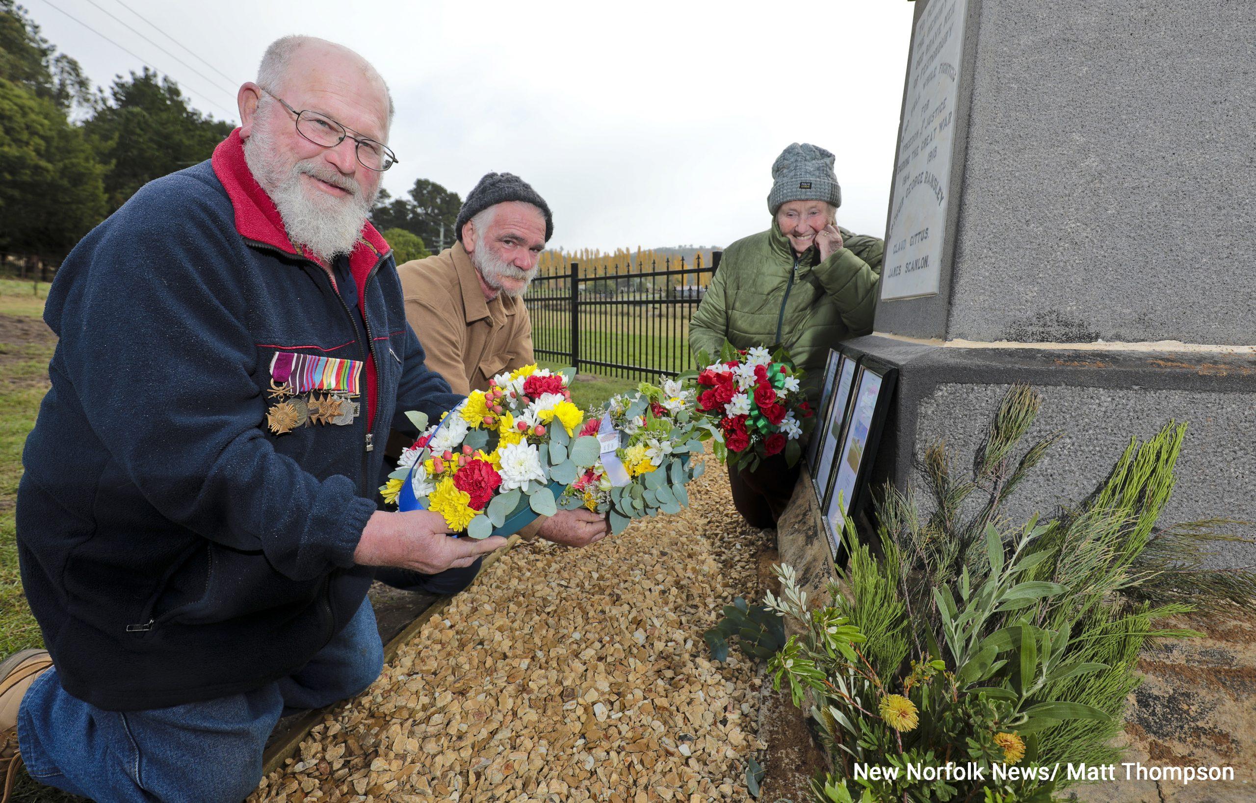 three people alongside a monument